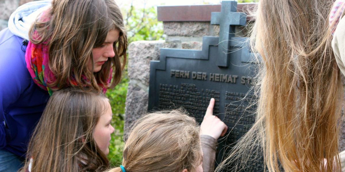Jugendliche lesen die Namen auf einer Gedenktafel